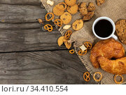 View of cookies, pretzels and croissants put on a table cloth with a cup of coffee on wooden surface. Стоковое фото, агентство Wavebreak Media / Фотобанк Лори