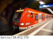 Germany, Frankfurt am Main - S-Bahn station underground, train enters (2020 год). Редакционное фото, агентство Caro Photoagency / Фотобанк Лори