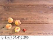 Несколько персиков на коричневом деревянном столе. Свободное место для текста. Стоковое фото, фотограф Наталья Гармашева / Фотобанк Лори