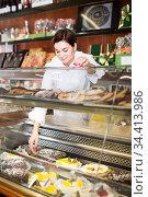 Positive woman seller showing best dessert to help. Стоковое фото, фотограф Яков Филимонов / Фотобанк Лори