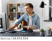 young man with guitar and computer at home. Стоковое фото, фотограф Syda Productions / Фотобанк Лори