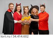 happy friends in halloween costumes over grey. Стоковое фото, фотограф Syda Productions / Фотобанк Лори
