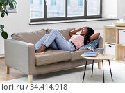 tired african american woman lying on sofa at home. Стоковое фото, фотограф Syda Productions / Фотобанк Лори