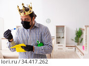Young male contractor cleaning the house in coronavirus concept. Стоковое фото, фотограф Elnur / Фотобанк Лори