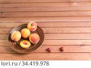 Несколько спелых персиков в тарелке на коричневом деревянном столе. Свободное место для текста. Стоковое фото, фотограф Наталья Гармашева / Фотобанк Лори