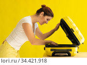 Caucasian woman going on vacation and packing suitcase on yellow background. Стоковое фото, фотограф Михаил Решетников / Фотобанк Лори