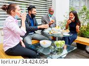 Junge Geschäftsleute in einer Pause essen zusammen am Tisch mit Mund... Стоковое фото, фотограф Zoonar.com/Robert Kneschke / age Fotostock / Фотобанк Лори