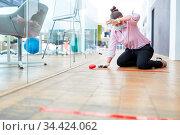 Geschäftsfrau markiert Büro Boden mit Klebeband für Abstand halten... Стоковое фото, фотограф Zoonar.com/Robert Kneschke / age Fotostock / Фотобанк Лори