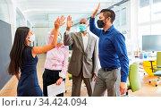 Business Team mit Mund-Nasen-Schutz beim High Five für Teamgeist ... Стоковое фото, фотограф Zoonar.com/Robert Kneschke / age Fotostock / Фотобанк Лори
