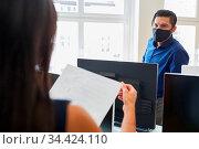 Zwei Geschäftsleute mit Mund-Nasen-Schutz arbeiten zusammen im Büro. Стоковое фото, фотограф Zoonar.com/Robert Kneschke / age Fotostock / Фотобанк Лори