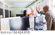 Team mit Mundschutz im Büro beim High Five geben zur Motivation nach... Стоковое фото, фотограф Zoonar.com/Robert Kneschke / age Fotostock / Фотобанк Лори