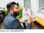 Business Mann mit Mundschutz am Kinn beim Snack essen in einem Café... Стоковое фото, фотограф Zoonar.com/Robert Kneschke / age Fotostock / Фотобанк Лори