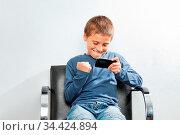 Kind gewinnt bei Handy-Spiel auf einem Smartphone. Стоковое фото, фотограф Zoonar.com/Robert Kneschke / age Fotostock / Фотобанк Лори