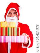 Weihnachtsmann mit roter Kapuze überreicht bunte Geschenke. Стоковое фото, фотограф Zoonar.com/Robert Kneschke / age Fotostock / Фотобанк Лори