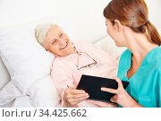 Krankenpflegerin liest einer bettlägerigen Seniorin Geschichten aus... Стоковое фото, фотограф Zoonar.com/Robert Kneschke / age Fotostock / Фотобанк Лори