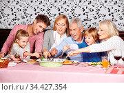Große Familie beim Abendessen langt hungrig in eine Schüssel. Стоковое фото, фотограф Zoonar.com/Robert Kneschke / age Fotostock / Фотобанк Лори