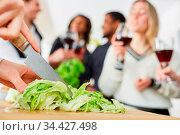 Eisbergsalat mit Messer schneiden für Essen mit Freunden in einer WG. Стоковое фото, фотограф Zoonar.com/Robert Kneschke / age Fotostock / Фотобанк Лори