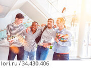 Glückliche Studenten lachen zusammen als Team in der Universität. Стоковое фото, фотограф Zoonar.com/Robert Kneschke / age Fotostock / Фотобанк Лори