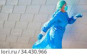 Ärztin in Bereitschaft mit Schutzkleidung läuft zu Notfall wegen ... Стоковое фото, фотограф Zoonar.com/Robert Kneschke / age Fotostock / Фотобанк Лори