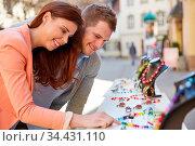 Glückliches Paar betrachtet Schmuck in der Auslage vor einem Juwelier. Стоковое фото, фотограф Zoonar.com/Robert Kneschke / age Fotostock / Фотобанк Лори