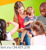 Lächelnde Kindergärtnerin und Kinder lesen gemeinsam ein Buch im ... Стоковое фото, фотограф Zoonar.com/Robert Kneschke / age Fotostock / Фотобанк Лори