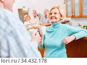 Lächelnde Rentnerin trinkt eine Tasse Kaffee beim Smalltalk auf einem... Стоковое фото, фотограф Zoonar.com/Robert Kneschke / age Fotostock / Фотобанк Лори