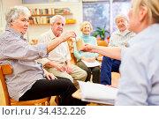 Psychotherapeutin und Senioren machen ein Spiel in einer Beschäftigungstherapie. Стоковое фото, фотограф Zoonar.com/Robert Kneschke / age Fotostock / Фотобанк Лори