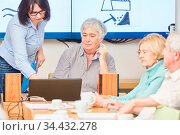 Dozentin mit Laptop und Senioren in einem VHS Kurs zur Erwachsenenbildung. Стоковое фото, фотограф Zoonar.com/Robert Kneschke / age Fotostock / Фотобанк Лори