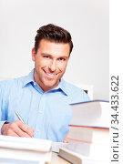 Lächelnder Student mit vielen Büchern lernt für Jura-Studium. Стоковое фото, фотограф Zoonar.com/Robert Kneschke / age Fotostock / Фотобанк Лори