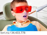 Kind bei Lasertherapie beim Zahnarzt mit geöffnetem Mund. Стоковое фото, фотограф Zoonar.com/Robert Kneschke / age Fotostock / Фотобанк Лори