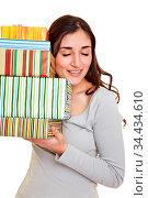 Junge Frau legt ihr Ohr an einen Stapel bunter Geschenke. Стоковое фото, фотограф Zoonar.com/Robert Kneschke / age Fotostock / Фотобанк Лори