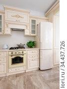 Modern spacioius beige colored luxury kitchen, clean design. Стоковое фото, фотограф Zoonar.com/Serghei Starus / easy Fotostock / Фотобанк Лори
