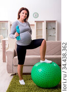Aged pregnant woman doing exercises at home. Стоковое фото, фотограф Zoonar.com/Elnur Amikishiyev / easy Fotostock / Фотобанк Лори