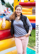 Toothy smiling woman portrait, wearing pink trousers and waistcoat, stands leaning to inflatable jump castle, outdoor portrait. Стоковое фото, фотограф Кекяляйнен Андрей / Фотобанк Лори