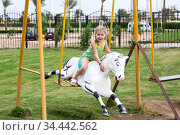Little girl sitting on harseback of children swing, swinging on playground. Стоковое фото, фотограф Кекяляйнен Андрей / Фотобанк Лори
