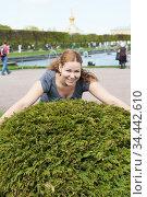 Portrait of happy Caucasian woman trying to embrace green bush in urban public park, looking at camera. Стоковое фото, фотограф Кекяляйнен Андрей / Фотобанк Лори