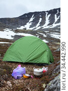 Food cooking on portable gas stove during hiking, green tent is on mountain valley for sleeping, mountains with severe weather and snow. Стоковое фото, фотограф Кекяляйнен Андрей / Фотобанк Лори