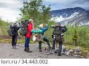 Team of Caucasian hikers looking at mountain top before starting their hiking route, mountaineering in snow mountains with one family. Стоковое фото, фотограф Кекяляйнен Андрей / Фотобанк Лори