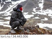 Caucasian teenage boy dressing warm hiking outfit for mountaineering, young man sitting on big stone and looking far away in mountains. Стоковое фото, фотограф Кекяляйнен Андрей / Фотобанк Лори