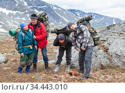 Tired backpackers with heavy backpacks standing in mountains, four mountaineers portrait with different ages. Стоковое фото, фотограф Кекяляйнен Андрей / Фотобанк Лори