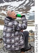 Man drinking energy drink on the mountain peak, one climber or mountaineer sitting on rock. Стоковое фото, фотограф Кекяляйнен Андрей / Фотобанк Лори