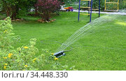Sprinkling the lawn with a watering device with a change of direction of water jets. Стоковое видео, видеограф Владимир Литвинов / Фотобанк Лори