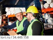 Logistik Arbeiter und Kommissionierer holen Waren in Industrie Lager... Стоковое фото, фотограф Zoonar.com/Robert Kneschke / age Fotostock / Фотобанк Лори