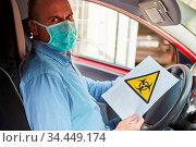 Autofahrer mit Biogefährdung Warnung bei Covid-19 Coronavirus Pandemie. Стоковое фото, фотограф Zoonar.com/Robert Kneschke / age Fotostock / Фотобанк Лори