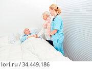 Alte Frau besucht ihren Mann im Krankenhaus mit der Hilfe einer Pflegekraft. Стоковое фото, фотограф Zoonar.com/Robert Kneschke / age Fotostock / Фотобанк Лори