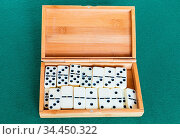 Set of white dominoes tiles in bamboo box on green baize table. Стоковое фото, фотограф Zoonar.com/Valery Voennyy / easy Fotostock / Фотобанк Лори
