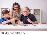 Three generations of family playing jigsaw puzzle game. Стоковое фото, фотограф Elnur / Фотобанк Лори
