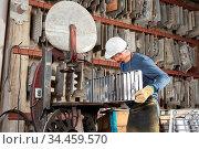 Mann als Arbeiter sucht eine passende Gussform im Lager einer Gießerei. Стоковое фото, фотограф Zoonar.com/Robert Kneschke / age Fotostock / Фотобанк Лори