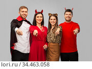 happy friends in halloween costumes over grey. Стоковое фото, фотограф Syda Productions / Фотобанк Лори
