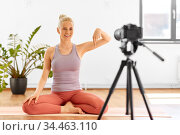 woman with camera streaming for yoga blog at home. Стоковое фото, фотограф Syda Productions / Фотобанк Лори